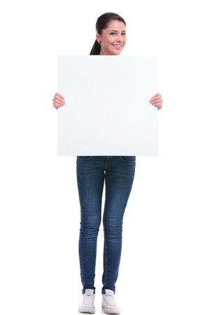 pannel: full length picture of a casual young woman holding a blank pannel with voth her hands and smiling to the camera. isolated on white background