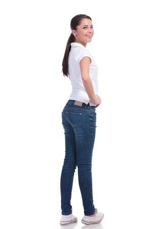 over the shoulder view: full length picture of a casual young woman standing with her back to the camera and holding a hand on her hip while looking over the shoulder at the camera and smiling. isolated on white background
