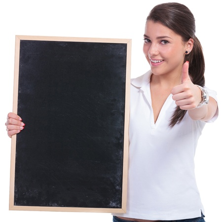 casual young woman holding a small blackboard and showing thumbs up while smiling to the camera. isolated on white background photo