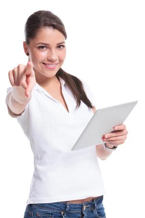 apontador: casuais jovem mulher segurando um tablet e apontando para a c Banco de Imagens