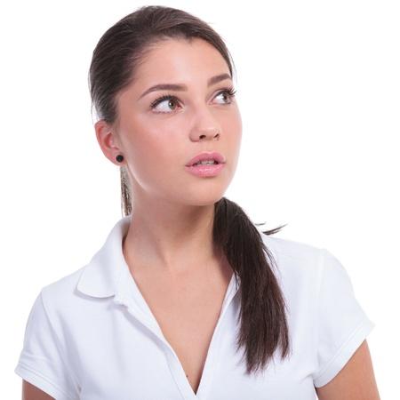při pohledu na fotoaparát: Příležitostné mladá žena hledá ve směru na straně, pryč od kamery. izolovaných na bílém pozadí Reklamní fotografie