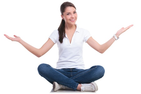 girl in jeans: casual young woman sitting with legs crossed and welcoming you. isolated on white background Stock Photo