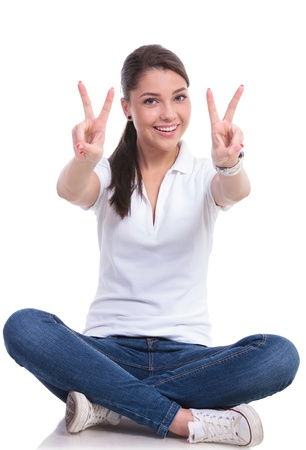 both: casual young woman sitting with legs crossed showing victory sign with both hands while smiling to the camera. isolated on white background