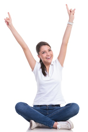 both: casual young woman sitting with legs crossed cheering with both hands pointing up while smiling to the camera. isolated on white background Stock Photo