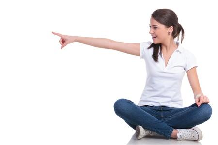 dedo apuntando: mujer joven casual sentado con las piernas cruzadas señalando y mirando a su lado con una sonrisa. aislado en fondo blanco Foto de archivo