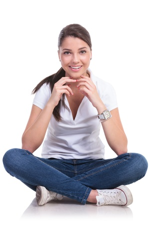 casual young woman sitting with legs crossed and looking at the camera with a smile on her face. isolated on white background photo