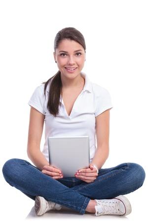 belles jambes: occasionnels jeune femme assise avec les jambes croisées et tenant une tablette tout en regardant la caméra avec un sourire. isolé sur fond blanc