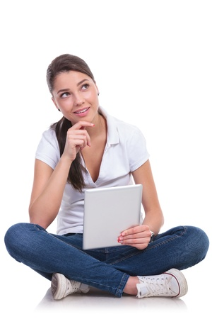 teen feet: casual young woman sitting with legs crossed and looking up pensively while holding her tablet. isolated on white background Stock Photo