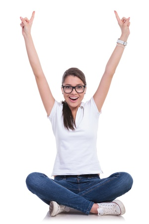 belles jambes: occasionnels jeune femme assise avec les jambes croisées et encourageant avec les deux index pointant vers le haut tout en souriant à la caméra. isolé sur fond blanc