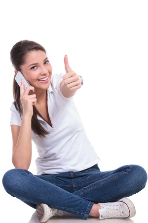 casual young woman sitting with legs crossed and talking on the phone while showing thumb up gesture and smiling at the camera. isolated on white background photo