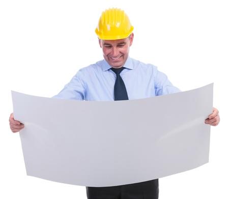 ambos: ingeniero senior mirando un plano que sostiene con ambas manos y sonriendo. aislado en fondo blanco
