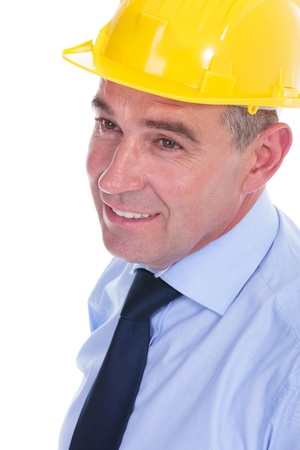 closeup portrait of a senior engineer with a helmet on his head, looking away from the camera and smiling. isolated on white background photo