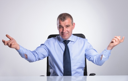 arms on chair: senior bussines man welcoming you with a smile from his desk. on gray background