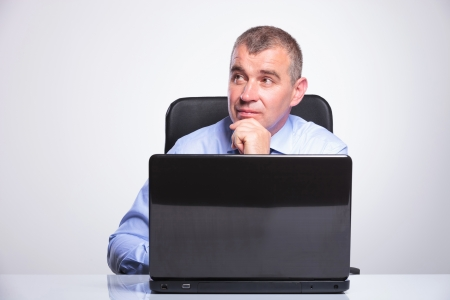 senior bussines man sitting at the desk, in front of the laptop and looking away pensively. on gray background Stock Photo - 20054503