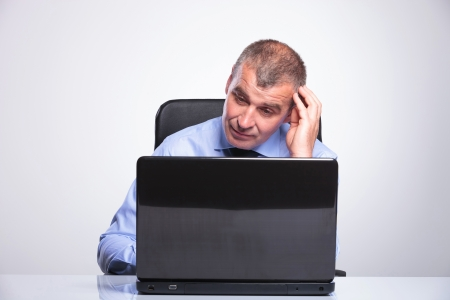 bored man: senior bussines man sitting at desk and looking at the laptop questioningly or bored.on gray background