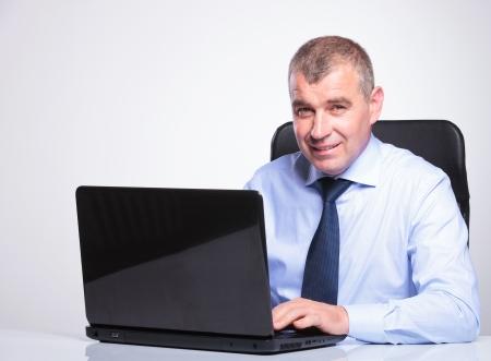 poner atencion: hombre mayor de los bussines en mesa de trabajo en su portátil mientras sonríe a la cámara. sobre fondo gris Foto de archivo