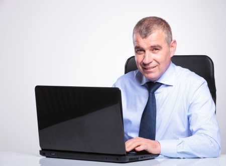 paying attention: senior bussines man at desk working on his laptop while smiling at the camera. on gray background