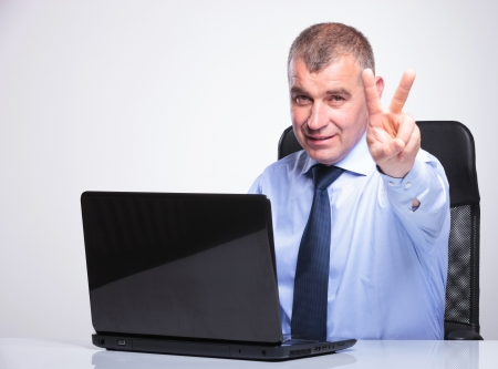mature businessman: senior bussines man sitting at hos desk behind his laptop and showing the victory sign and looking at the camera.on gray background