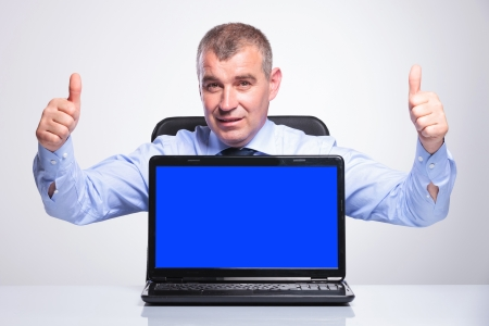 senior bussines man sitting at the desk, in front of a laptop with blank blue screen and showing both thumbs up while smiling at the camera.on gray background  photo