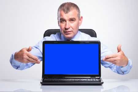 senior bussines man at the desk and presenting his laptop with blue screen. on gray background  photo