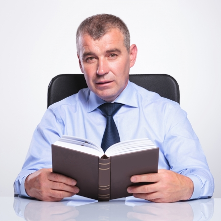 senior bussines man sitting at the desk and holding a book while looking at the camera. isolated on white photo