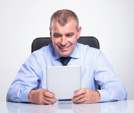 senior bussines man holding and looking at his tablet while at the office with a smile on his face . on gray background  photo