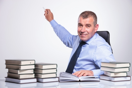 senior bussines man at the desk with many books showing something in the back with some chalk while looking at the camera with a smile on his face. on gray background  photo