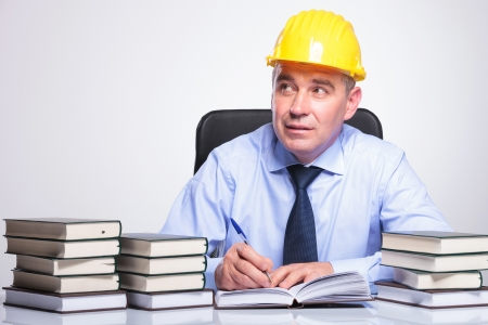 architect office: senior bussines man with helmet, sitting at a desk full of books and writing while contemplating, looking away from the camera. on gray background