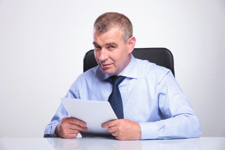senior bussines man sitting at the desk with some papers in his hands and looking at the camera . on gray background  photo