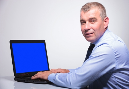 rear view of a senior bussines man working at a laptop with a blue screen and looking at the camera. on gray background  photo