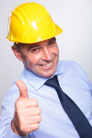 high angle picture of a senior bussines man wearing a helmet and showing thumb up and a smile at the camera.on gray background photo