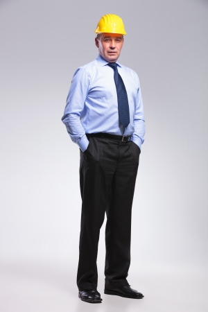 full length picture of a senior bussines man with a yellow helmet holding his hands in his pockets while looking at the camera. on gray background
