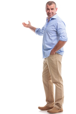 full length picture of a casual senior man presenting something in the back, with a hand in his pocket while looking at the camera. isolated on white background Stock Photo