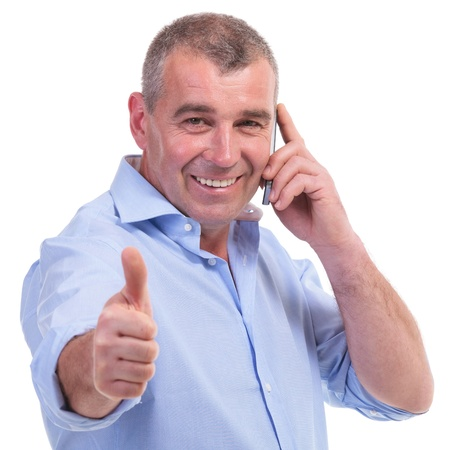 casual senior man showing thumb up sign while talking on the telephone and smiling for the camera. isolated on white background photo