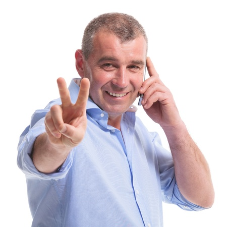 casual senior man talking on the phone and showing the victory sign while smiling for the camera. isolated on white background