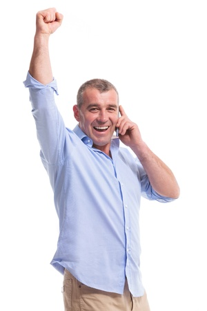casual senior man talking on the phone and cheering while looking at the camera. isolated on white background photo
