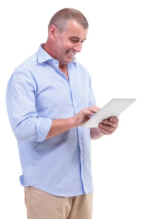 latin man: casual senior man working on his tablet and smiling. isolated on white background Stock Photo