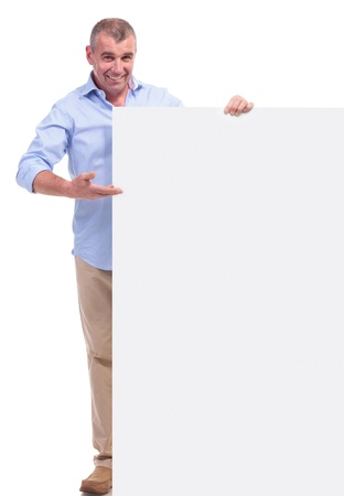 full length picture of a casual senior man presenting a blank board while smiling for the camera. isolated on white background photo