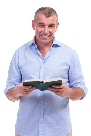predicador: Hombre mayor ocasional con un libro abierto y una sonrisa para la c�mara. aislado en fondo blanco