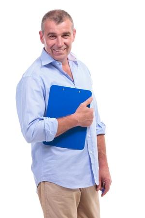 questionaire: hombre mayor casual la celebraci�n de un portapapeles y sonriendo para la c�mara. aislado en fondo blanco