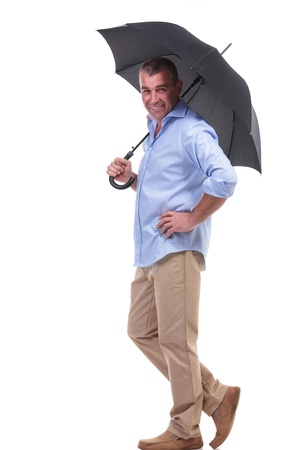 brolly: full length picture of a casual senior man holding an opened umbrella on his shoulder and a hand on his hip while smiling for the camera. isolated on white background