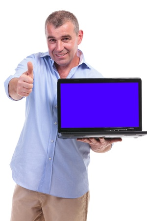 casual senior man presenting a laptop with a blue empty screen and showing the thumbs up gesture while smiling for the camera. isolated on white background Stock Photo - 20054516