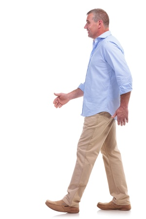 stepping: side view of a casual senior man walking and looking forward. isolated on white background