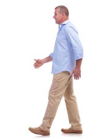senioren wandelen: zijaanzicht van een casual senior man lopen en kijken ernaar. geïsoleerd op witte achtergrond Stockfoto