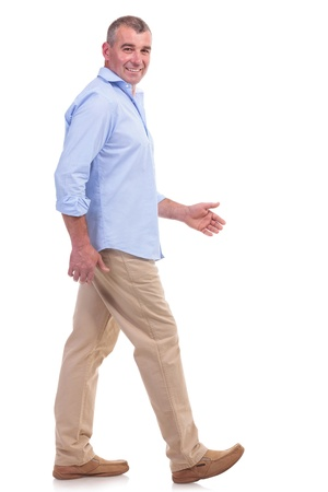 side view of a casual senior man walking forward and looking at the camera. isolated on white background