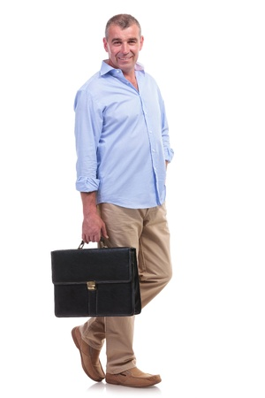 full length picture of a casual senior man standing with a briefcase in his hand and holding the other hand in his pocket while smiling for the camera. isolated on white background photo