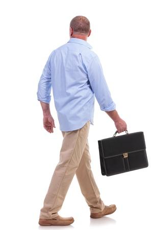volle lengte foto van een toevallige senior man lopen weg van de camera met een koffer in zijn hand. geïsoleerd op witte achtergrond Stockfoto