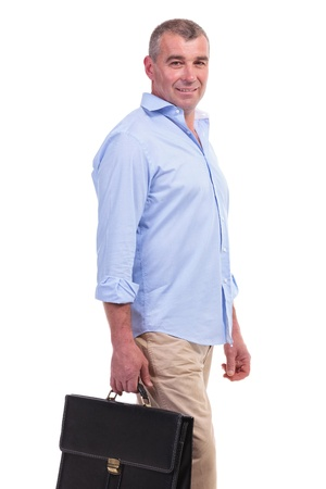 carying: casual senior man holding a suitcase in his hand and smiling for the camera. isolated on white background Stock Photo