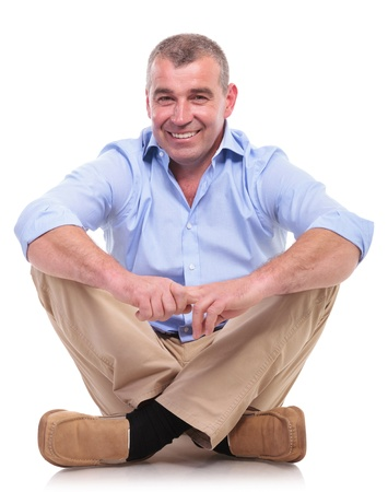 crossed legs: casual senior man sitting on the floor with his legs crossed holding his hands together and smiling for the camera . isolated on white background