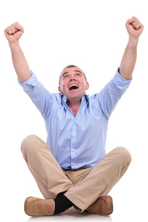 casual senior man sitting on the floor with his legs crossed and cheering with his hands in the air while screaming. isolated on white background photo